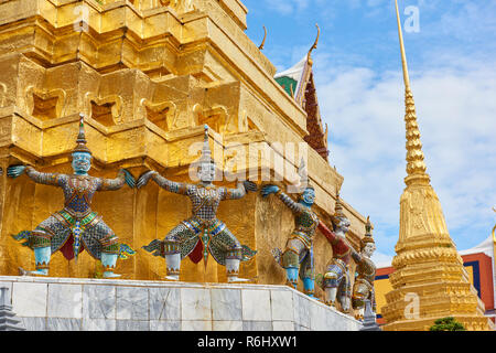 Golden Yaksha statues surrounding a pagoda in the Grand Palace in Bangkok, Thailand. The demon-gods statues are a common sight in Buddhist temples in  - Stock Image