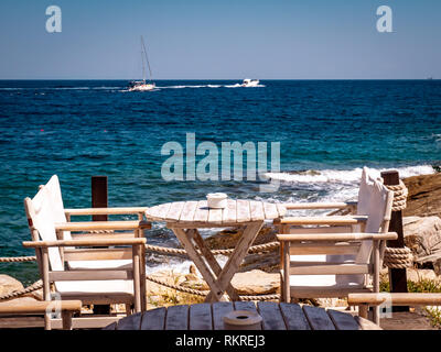 Greek tavern near the sea with wood chairs and table painted in white - Stock Image
