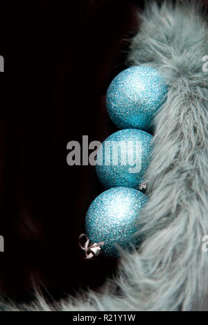 Three blue holiday ornaments in a vertical row on black copy space - Stock Image