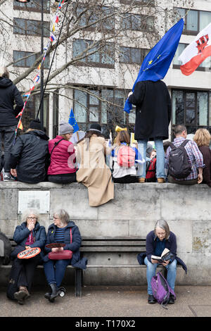 People sat on bench and wall, People's Vote March, London, England - Stock Image