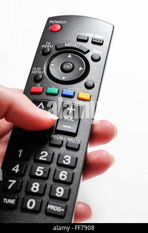 Picture of television remote control being held by a female left hand over a white background - Stock Image