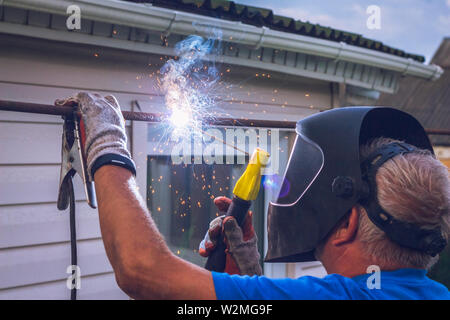 The welder works with a metal structure in the suburban area - Stock Image