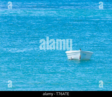 small white boat sitting in a blue sea - Stock Image