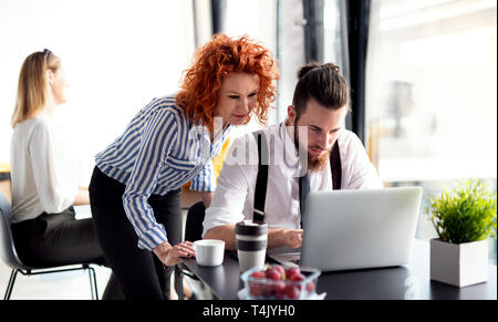 A group of cheerful business people sitting in an office, using laptop. - Stock Image