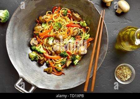 Stir-fry noodles with vegetables in wok pan on black stone background. Top view, flat lay - Stock Image