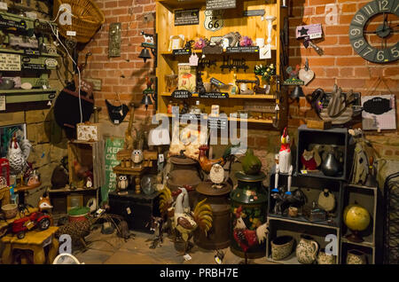 Interior of a rural garden centre and antique shop with a collection of vintage and reproduction garden tools ornaments and bric a brac - Stock Image