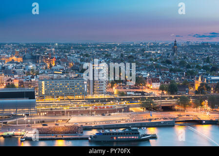Skyline Amsterdam, Central Station, bike parking, train, church &Westertoren, palace 'Paleis op de Dam', Schiphol,  light trails of landing airplanes. - Stock Image