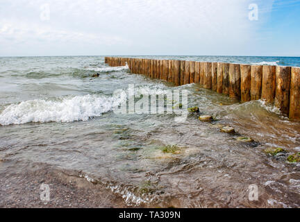 seascape with the waves crashing on breakwater on sunny summer day - Stock Image