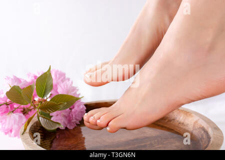 Girl bare feet with french pedicure on nails on wooden bowl with water and pink flower in beautiful and spa salon. Close up, selective focus - Stock Image