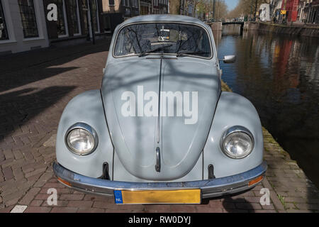 Netherlands, Gouda, 2017, An old volkswagen beetle, parked along the side of a canal or grachten. In the background the typical architecture of the ci - Stock Image