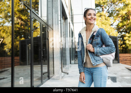 Beautiful young brunette woman wearing jacket, carrying backpack walking outdoors - Stock Image