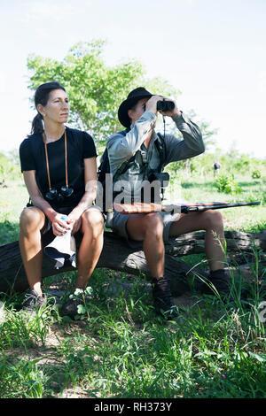 Couple sitting on log - Stock Image