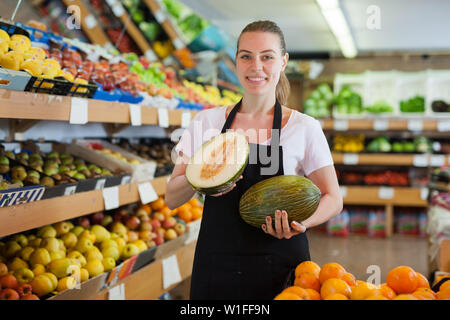 Young woman holding two fresh melon during offering fresh fruits on the store - Stock Image