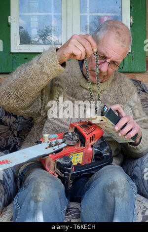 mature man working on a chainsaw to replace the blunt chain with a sharp one zala county hungary - Stock Image