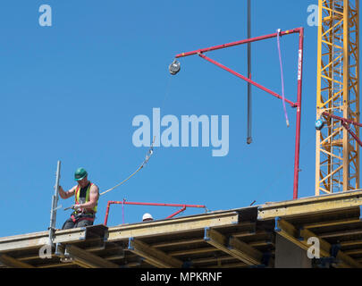 A building construction worker wearing a safety harness attached to an Alsina Fall Arrest System, England, UK - Stock Image