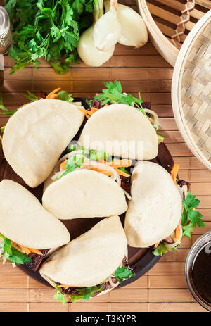 Gua bao, steamed buns with pork belly and vegetable. Asian cuisine. Top view - Stock Image