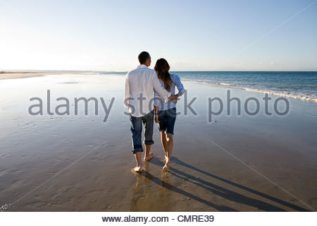 Couple walking on beach - Stock Image