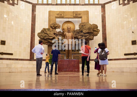 Visitors stand in front of statue of president Ho Chi Minh in the lobby of the museum with the same name. The museum houses a collection of items and  - Stock Image