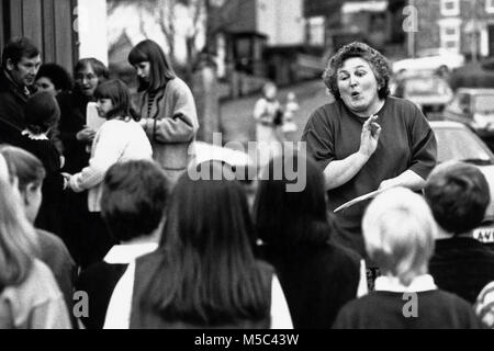 Music teacher taking childrens choir in practice outside at small eisteddfod in village hall at Llandudoch St Dogmaels - Stock Image