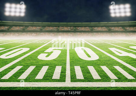 Close up of American football stadium field with yard line markings and spotlight with blurred background. - Stock Image