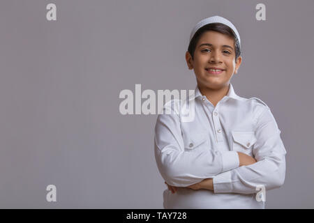 young Muslim boy wearing cap folding hands and smiling - Stock Image