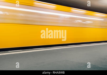 Yellow U-Bahn subway train arriving at a station in Berlin, Germany - Stock Image