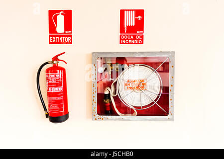 Fire extinguisher fire hose emergency equipment in case of fire Fire extinguisher on wall Fire extinguisher mounted - Stock Image