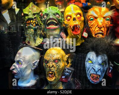 Scary masks for sale in a shop window. It must be Halloween time?! Photo Credit - © COLIN HOSKINS. - Stock Image