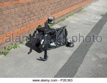 Child's buggy abandoned in street.  Damaged children's buggy with some wheels missing on pavement in Garston, Liverpool, UK. - Stock Image