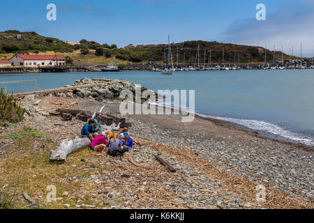 people, family, tourists, visitors, sitting on beach, beach, Fort Baker, city of Sausalito, Sausalito, Marin County, California, United States, North  - Stock Image