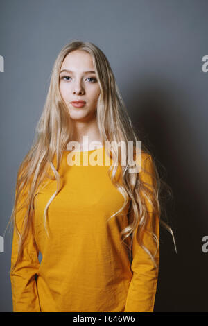 serene teenage girl with very long blond hair against gray background - Stock Image