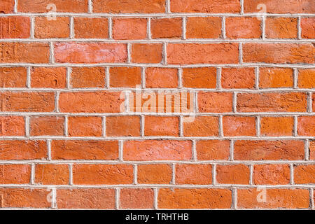 Red rough brick wall close up. Texture and background - Stock Image