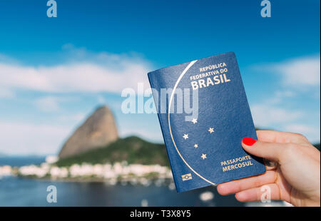 Hand holding Brazilian passport with SugarLoaf Mountain in Rio de Janeiro, Brazil in background - digital composite - Stock Image