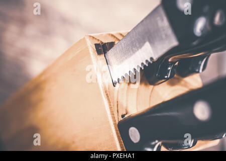 Macro Of A Jagged Steak Knife Half Pulled Out Of A Kitchen Knive Block On A Table - Stock Image