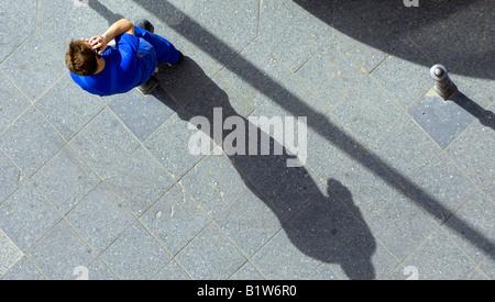 workman sitting shadow mobile phone berlin germany deutschland speaking talking sidewalk pavement aerial view - Stock Image