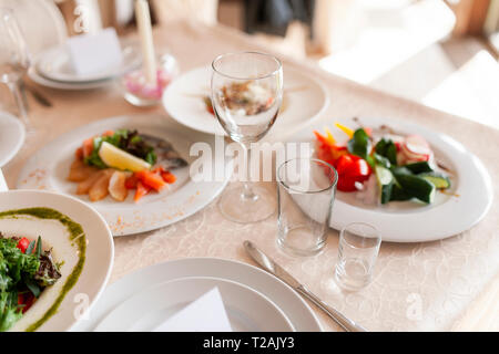 Drinking glasses and food on dining table during wedding - Stock Image