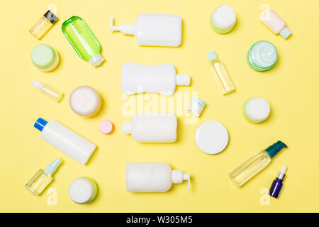 Group of plastic bodycare bottle Flat lay composition with cosmetic products on yellow background empty space for you design. Set of White Cosmetic co - Stock Image