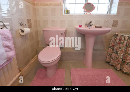An old fashioned pale pink coloured bathroom suite - Stock Image