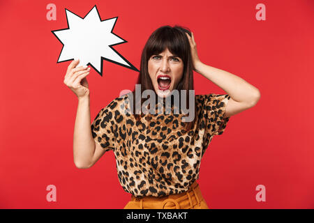 Photo of emotional brunette woman 30s dressed in stylish outfit screaming and holding blank speech bubble isolated over red background - Stock Image
