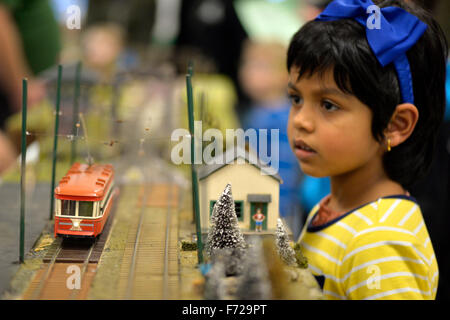 Bethpage, New York, USA. 22nd November 2015. Visitors watch as a colorful orange and beige O-Gauge trolloy passes - Stock Image