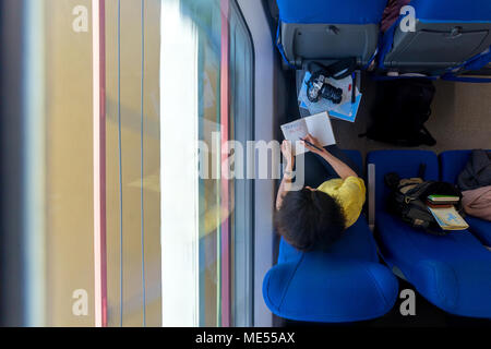 young woman loking in diary and writing words travel blog train during her traveling in train view from above copy space - Stock Image