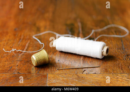 Thimble, a needle and a spool of white thread on an antique wood veneer full of cracks. Selective focus. Closeup. - Stock Image