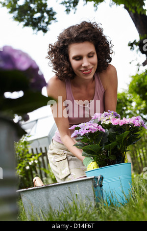 portrait of young woman planting flowers in the garden - Stock Image