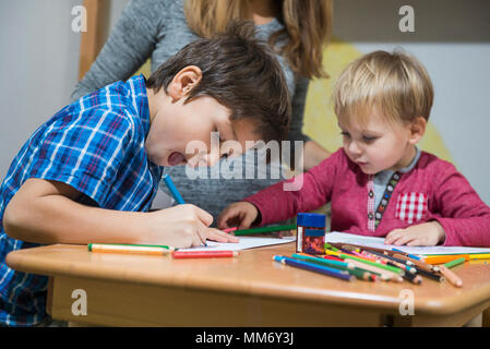 Brothers enjoying with colored pencils, Munich, Germany - Stock Image