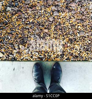 Cigarette butts outside an office building in the smoking zone - Stock Image
