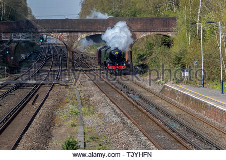 The iconic steam locomotive Flying Scotsman pictured passing through the quiet Hampshire village of Winchfield after a tour on the Swanage Railway. - Stock Image