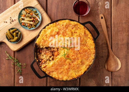 Shepherd's pie with pickles, herbs, and red wine, shot from above on a dark rustic wooden background - Stock Image