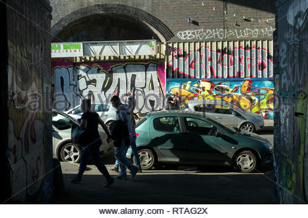 Parked cars and graffiti, underneath the railway arches in Digbeth, central Birmingham, West Midlands, UK. - Stock Image
