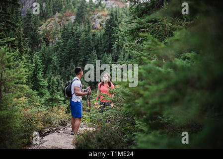 Couple hiking on remote trail in woods - Stock Image