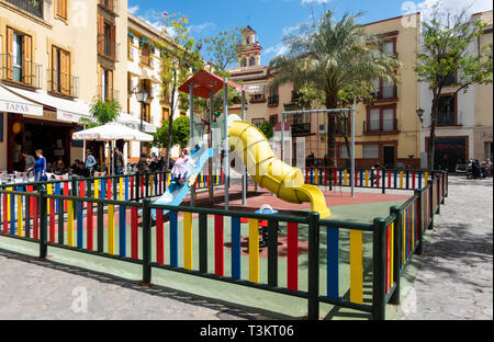 Girl climbing up a slide in a playground in Seville - Stock Image